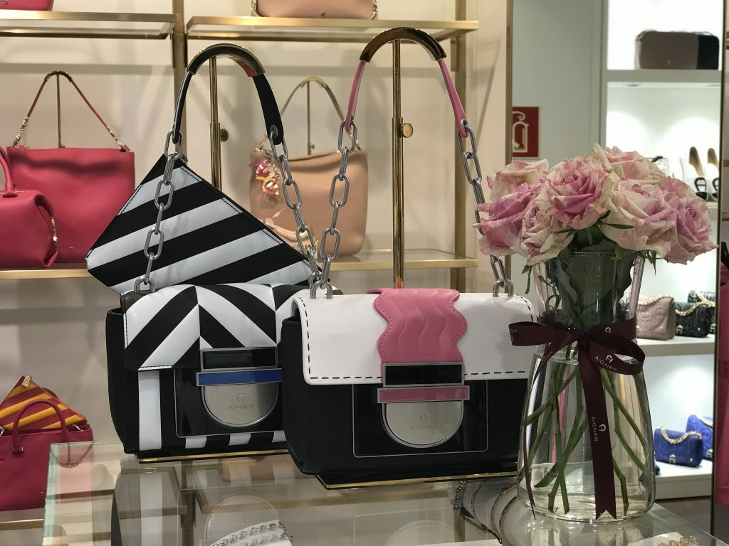 #AIGNERLOVE - DUESSELDORF Aigner shop, May 2018, Model and Blogger Alexandra Lapp wearing the it-bag Aigner Candice bag S in pink with black and white combined with the Love shoulder strap.