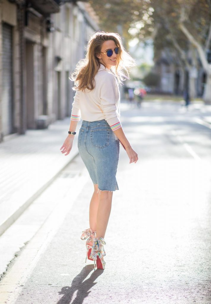 BARCELONA, SPAIN - NOVEMBER 27: Alexandra Lapp wearing a white cashmere hoodie with colored flower applications from Heartbreaker, high rise jeans skirt with slit Adriano Goldschmied, red little purse bag with gold chain from Christian Louboutin, peep-toe pump Christian Louboutin with a long satin bow, sunglasses with round blue shades from Mykita on November 27, 2017 in Barcelona, Spain.