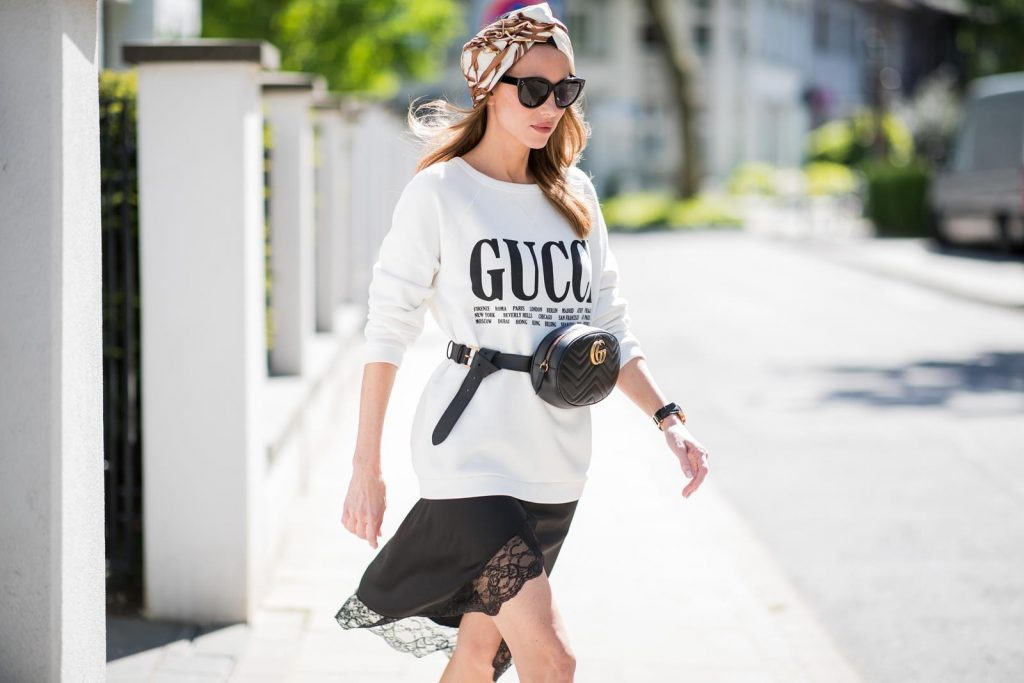 Alexandra Lapp wearing a Gucci Belt Bag Look with a white crew-neck cotton sweatshirt by Gucci, black double layered lace skirt by Zara , the black GG Marmont matelasse belt bag in black, black white striped So Kate pumps by Christian Louboutin, a vintage print silk scarf turban by Gucci, Portugieser watch by IWC and black Celine Audrey sunglasses on May 5, 2018 in Duesseldorf, Germany.