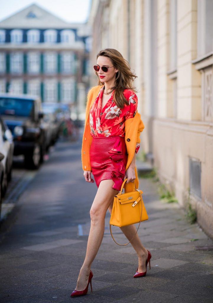 Alexandra Lapp wearing Hawaiian Silk Blouse in a kimono shape with all-over print by Jadicted, the Evangelista knitted cardigan by Ganni in turmeric orange, ruffled mini skirt in red leather by Magda Butrym, a Hermes Kelly bag in orange, Gianvito Rossi red patent pumps and gold mirrored Thom Browne sunglasses in red on May 6, 2018 in Duesseldorf, Germany.