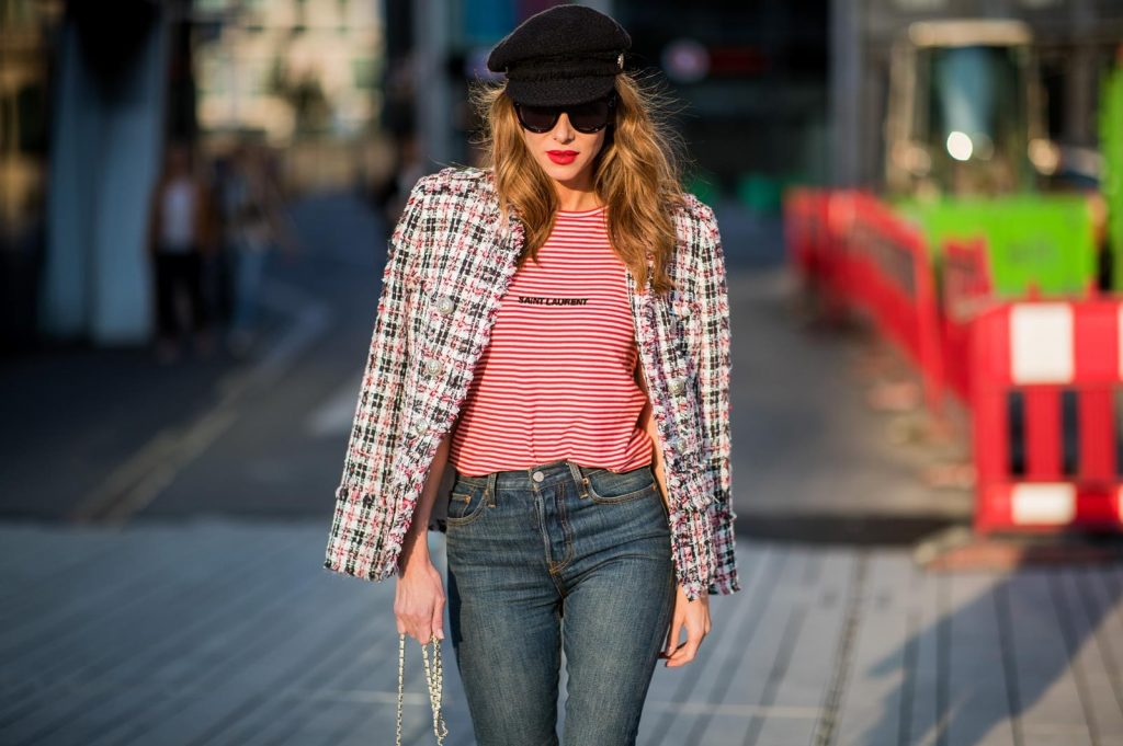 Alexandra Lapp wearing a striped shirt look with Saint Laurent Logo jersey T-Shirt in red-white, a white/blue/red Tweed Jacket by Balmain, dark blue Levis Super Skinny jeans, Prada flame shoes, the Chanel Perfume Bottle Bag in clear plexiglass, vintage Chanel Bakerboy cap and black Celine sunglasses on May 3, 2018 in Duesseldorf, Germany.