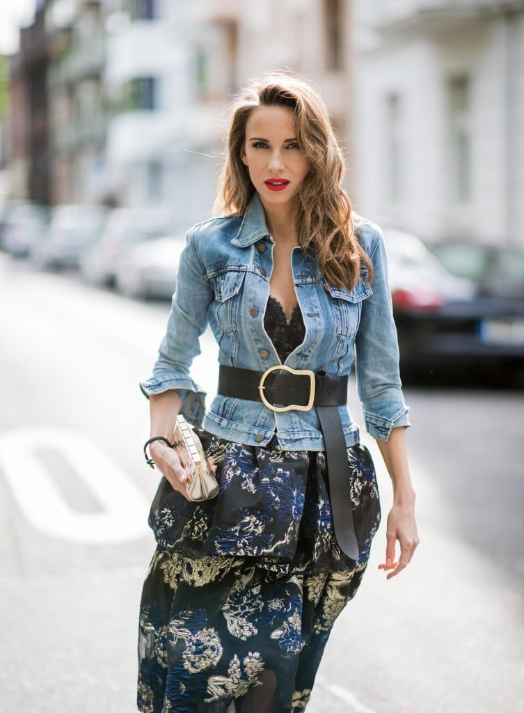 Alexandra Lapp wearing a Marchesa Notte dress with tiered corded lace and brocade in a mix of black, midnight-blue and gold by Marchesa Notte, blue trucker denim jacket by Levis, a gold buckle belt by Dorothee Schumacher, black Nosy t-bar Christian Louboutin sandals with a studded strap, handmade bracelet with rosegold fleur de lis lock by Coerlys and a vintage Chanel clutch in gold on May 3, 2018 in Duesseldorf, Germany.