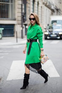 Alexandra Lapp wearing a lingerie look with a satin black skirt with lace around the rim from Zara, a green knit pullover from H&M, a black waist belt with large buckle from Dorothee Schumacher, black boots from Isabel Marant, a green light coat from Stella McCartney, black sunglasses from Celine and a cross body bag with crystal flowers from MCM is seen on February 27, 2018 in Paris, France.