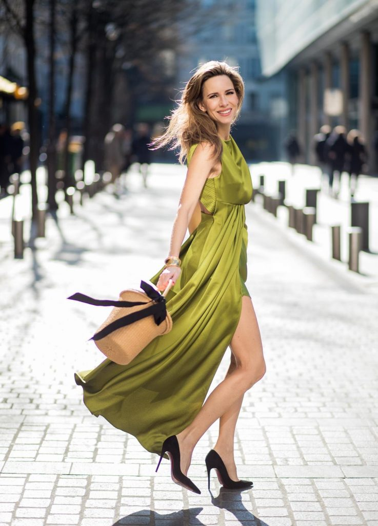 Alexandra Lapp is seen wearing an asymmetric layered silk dress from Off-white in green with a basket bag from Sensistudio with a black bow and black pumps from Christian Louboutin on February 28, 2018 in Paris, France.