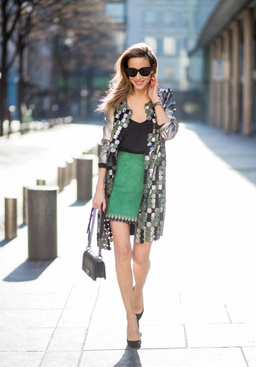 Alexandra Lapp wearing a silver coat from Yves Salomon with silver, green and black round leather parts with studs on the front, a short green suede leather skirt with blue and light grey pieces around the bottom line with studs by Yves Salomon, a black satin top from Jadicted, a black Chanel boy bag, black suede pumps by Christian Louboutin and black Celine sunglasses during Paris Fashion Week Womenswear Fall/Winter 2018/2019 on March 3, 2018 in Paris, France.