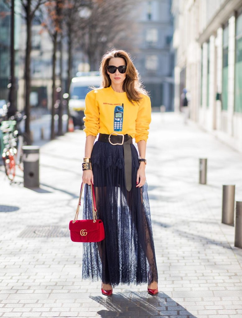 Alexandra Lapp in handmade print Wodka Ogurez sweater in yellow with handmade Nokia phone print, long dark blue Self-Portrait lace dress underneath, Dorothee Schumacher waist belt with big golden buckle, red patent Gianvito Rossi pumps, Chanel bracelet with golden CC sign, golden vintage Chanel bracelet, red velvet Gucci Marmont bag and Celine Audrey sunglasses during Paris Fashion Week Womenswear Fall/Winter 2018/2019 on March 3, 2018 in Paris, France.