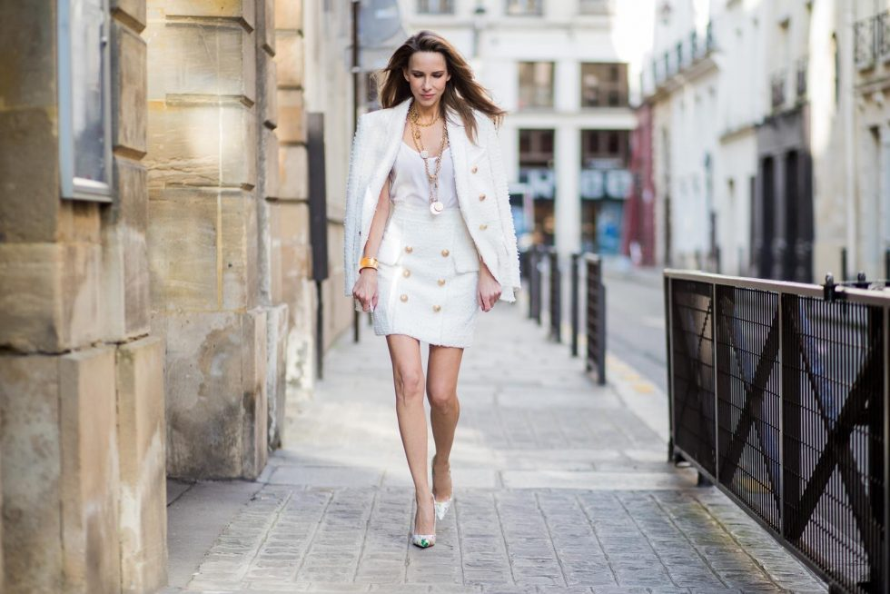 Alexandra Lapp in a full Balmain costume - a white tweed blazer with golden buttons and a matching tweed mini skirt with golden buttons both Balmain, a white silk top from Jadicted, heels from Christian Louboutin and Vintage necklaces from Chanel during Paris Fashion Week Womenswear Fall/Winter 2018/2019 on March 4, 2018 in Paris, France.
