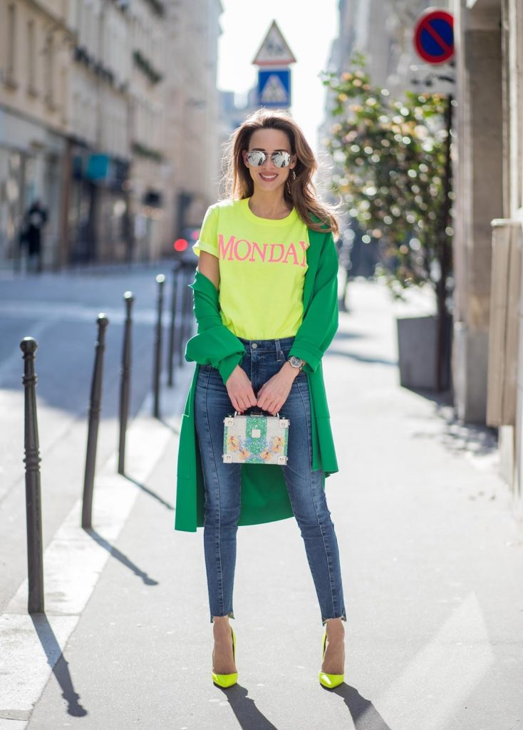 Alexandra Lapp in Mondays Statement Shirt Look wearing a yellow neon t-shirt with pink letters writing Monday by Alberta Ferretti, a blue pair of AG Jeans, a green coat from Stella McCartney, yellow neon pumps by Christian Louboutin, the Berlin cross body bag with crystal flowers from MCM and sunglasses by Le Specs during Paris Fashion Week Womenswear Fall/Winter 2018/2019 on March 5, 2018 in Paris, France.