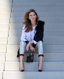 Model and Blogger Alexandra Lapp wearing silver denim pants from Airfield, black knit and fur cape from Airfield, black Boy Bag from Chanel, Chanel vintage necklace, silver sunglasses by Le Specs, white silk shirt from Jades and black lacquer Pigalle pumps from Christian Louboutin.