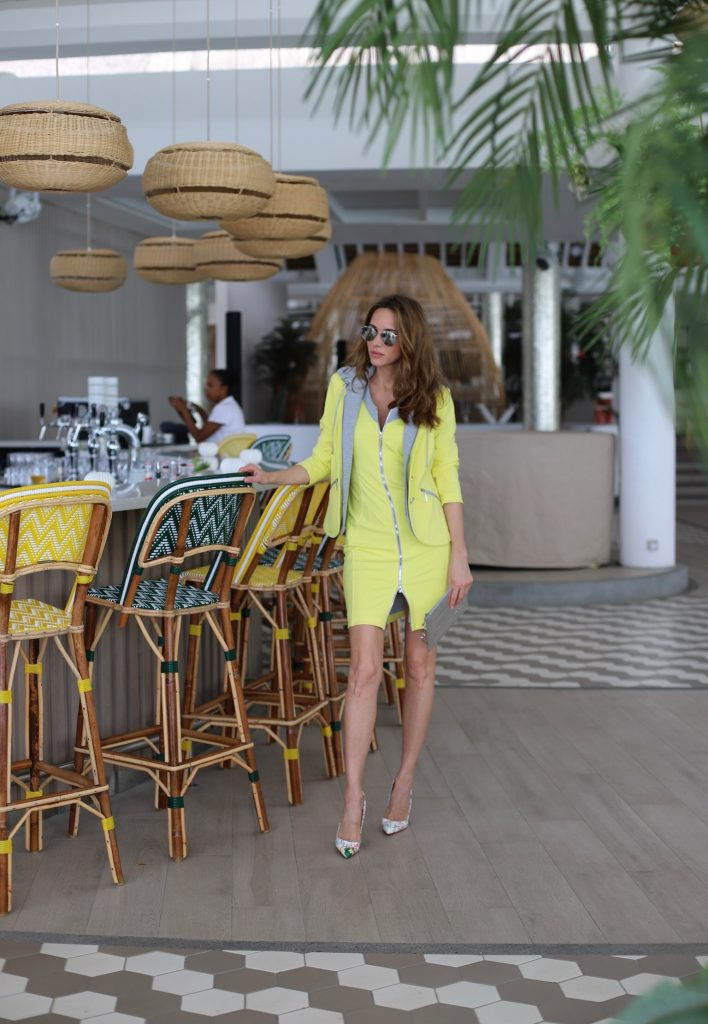 Alexandra Lapp in Yellow Mania wearing a yellow shift dress with zipper & a yellow como-blazer with hood, So Kate Loubitag red sole pumps with scribbled drawings, Louis Vuitton Monogram Miroir Pochette Plat Pouch and mirrored silver Aviator Le Specs seen on Mauritius during a press tour in April 2018.