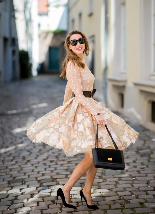 Alexandra Lapp wearing a pastel floral dress as seen in a lace embroidered mini dress by Lana Mueller, a gold buckle belt by Dorothee Schuhmacher, a numero deux edition in trio black by Polène, black Christian Louboutin pumps, black Celine sunglasses and a black leather bracelet by Coerlys on May 4, 2018 in Duesseldorf, Germany.