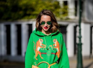 Alexandra Lapp in a Hermès Kelly Look wearing a green tiger print Gucci logo hoodie, a red pleated skirt by SET, a Hermes Birkin 30 bag in orange, Pigalle Follies pumps by Christian Louboutin and green mirrored Ray Ban sunglasses on May 3, 2018 in Duesseldorf, Germany.