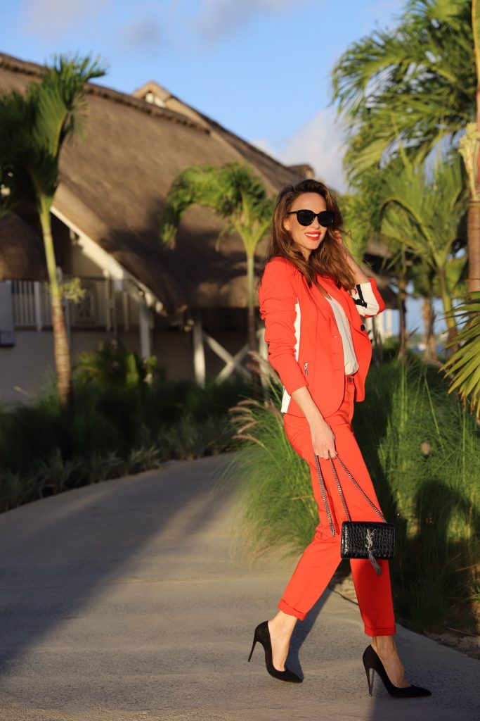 Model & Blogger Alexandra Lapp in Red Vibes wearing a red suit from Airfield, a white silk top from Jadicted, Christian Louboutin black suede pumps, a small Kate Tassel Yves Saint Laurent handbag in black and black Céline sunglasses.