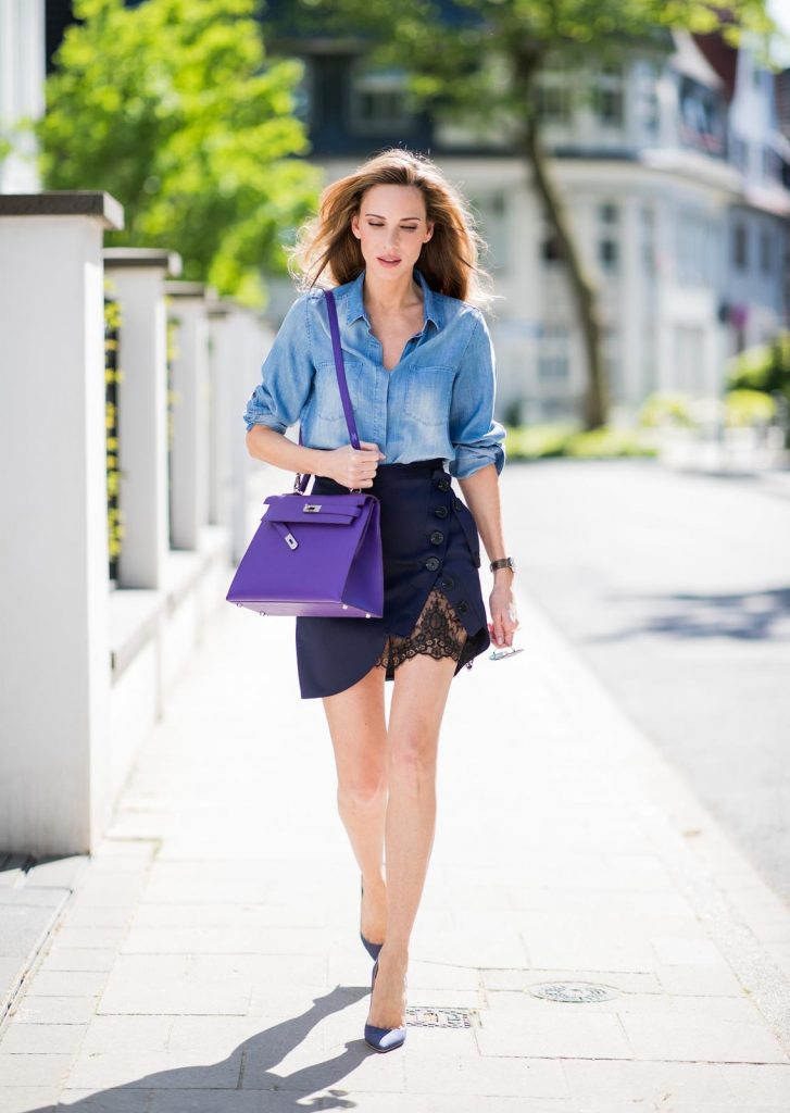 Alexandra Lapp in Hermès Addiction wearing a blue satin skirt with lace by Self-Portrait, a light blue denim shirt by H&M, a purple Kelly bag by Hermès, Denim Jazz Calf So Kate pumps by Christian Louboutin and purple mirrored Aviator sunglasses by Ray Ban on May 5, 2018 in Duesseldorf, Germany.