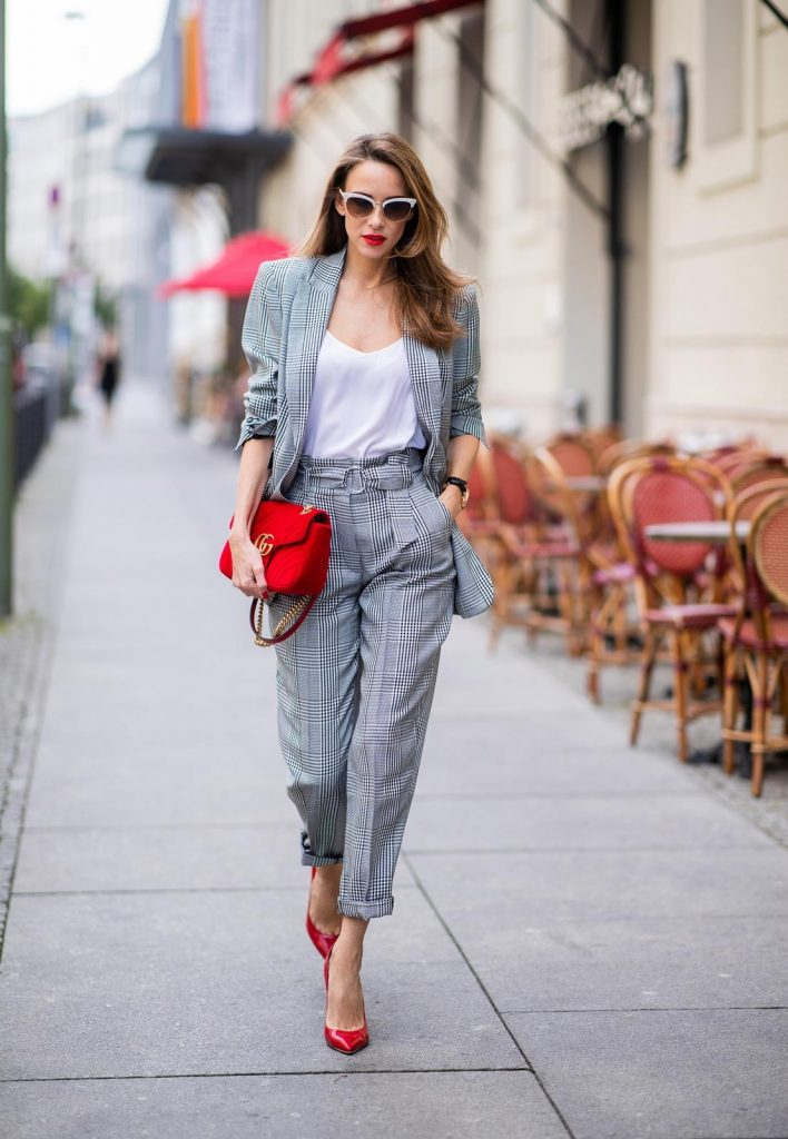 Alexandra Lapp for Big Dream | Riani wearing a checkered suit combination in black and white with a long blazer and high waist pants with an integrated belt both from Riani, a white silk top from Jadicted, red lacquer Gianvito Rossi pumps, red velvet GG Marmont Gucci handbag, vintage Gucci sunglasses and an IWC watch during the Berlin Fashion Week July 2018 on July 6, 2018 in Berlin, Germany.