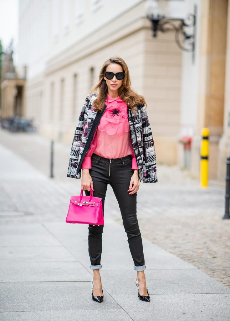 Alexandra Lapp in Birkin Bag Mini Look wearing a short checked colorful jacket with zipper from Airfield, transparent pink blouse with a big flower around the neck from Gucci, black Jeggins by Airfield, Dior slingback pumps in black with a J adior ribbon, a pink mini Birkin bag from Hermes, black Celine sunglasses and IWC watch during the Berlin Fashion Week July 2018 on July 6, 2018 in Berlin, Germany.