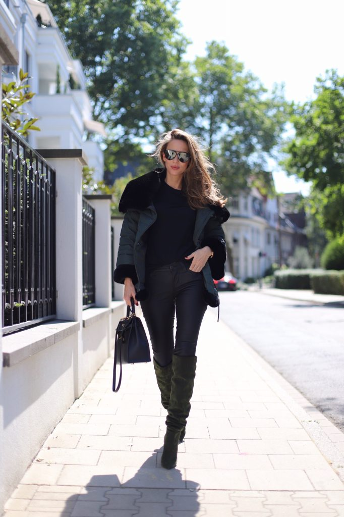 Model and Blogger Alexandra Lapp in a Faux Fur Jacket Look wearing a black down jacket with faux fur by Airfield, black leather pants by SET, black T-Shirt by James Perse, dark green leather overknee boots by Saint Laurent, black Kelly bag by Hermès and black Audrey sunglasses from Céline.