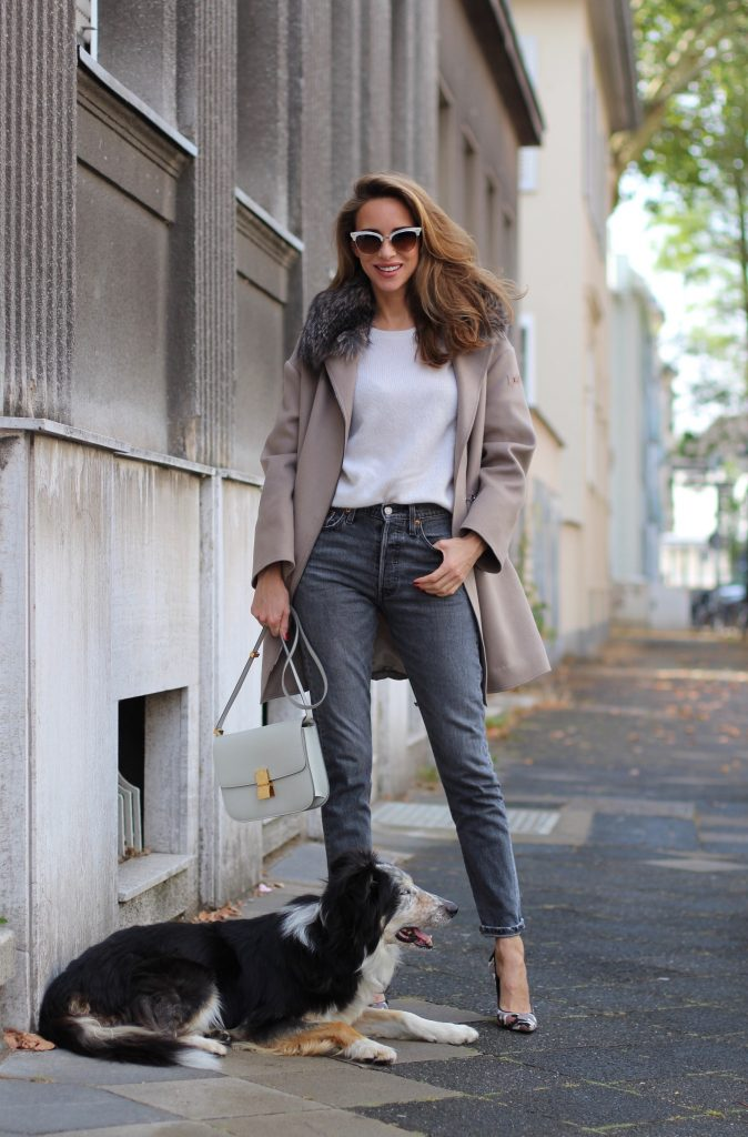 Model and Blogger Alexandra Lapp wearing a Céline Box Bag Look with a wool coat with fur collar in taupe, a light white wool sweater by Zara, grey Levi's jeans, camouflage Gianvito Rossi pumps, vintage Gucci sunglasses and a light grey Céline box bag in Düsseldorf, Germany.