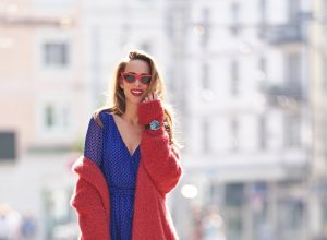 Model and blogger Alexandra Lapp with IWC Watches wearing a blue Polka-dot silk-blend dress by Valentino, Elado Cashmere and Silk-blend Cardigan in red by The Row, red Gg Marmont Quilted Leather Backpack by Gucci, red Céline Cat-Eye Sunglasses, red Gianvito Rossi heels, IWC Portugieser Chronograph and the Portofino Automatic Limited Edition by IWC.