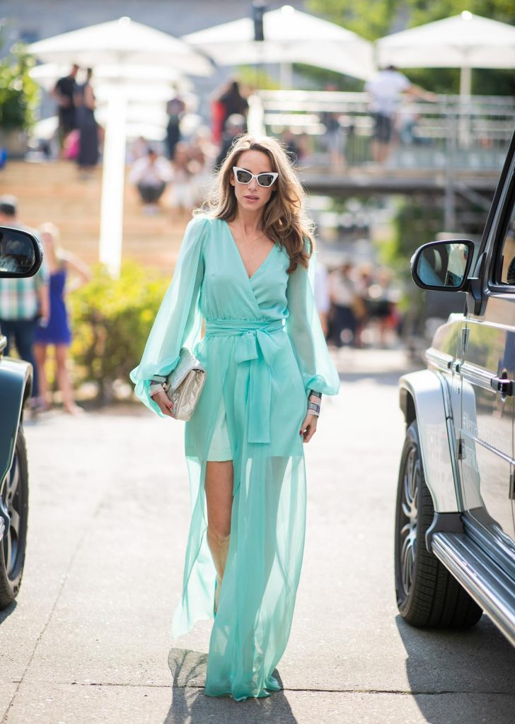 Alexandra Lapp in a turquoise dress wearing a long shine through dress in turquoise by Lana Mueller, a 2.55 silver handbag by Chanel, two tone Manolo Blahnik heels in silver turquoise and white Victoire sunglasses by Saint Laurent seen outside Lana Mueller during the Berlin Fashion Week July 2018 on July 5, 2018 in Berlin, Germany.