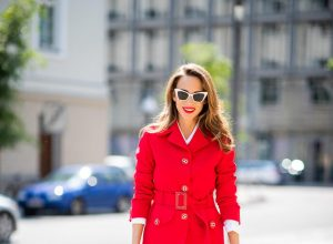 Alexandra Lapp in a Suit Style wearing a red suit combination in bright red with high waist pants with an attached belt and a slim cut blazer with an integrated waist belt, and a white shirt and a short loose knit wool coat in blue, red and white from Steffen Schraut, white snake pumps from Christian Louboutin, white and black cat-eye sunglasses by Saint Laurent and a white handbag from Roger Vivier with a golden buckle and chain seen during the Berlin Fashion Week July 2018 on July 5, 2018 in Berlin, Germany.