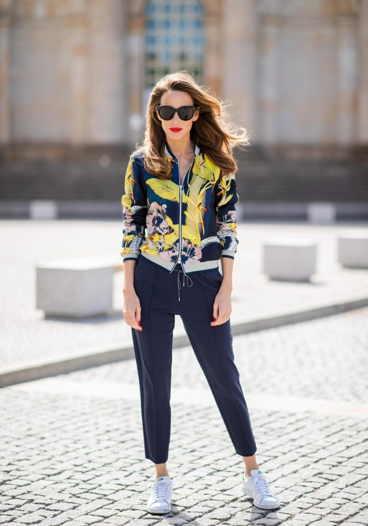 Alexandra Lapp in a Floral Jacket | Yellow Coat Look is seen wearing a blouson jacket with floral print, blue drawstring pants and a bright yellow duffle coat with a yellow fur hood from Airfield, Céline sunglasses in black, white Stan Smith Adidas sneakers with green details during the Berlin Fashion Week July 2018 on July 6, 2018 in Berlin, Germany.