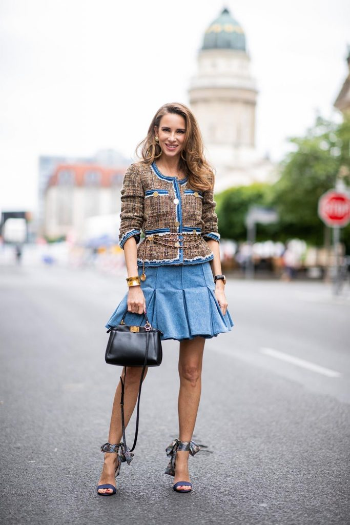 Alexandra Lapp in a Pleated Denim Skirt Look wearing a short tweed boucle jacket with denim from Steffen Schraut, a denim shirt from H&M, a denim pleated skirt from Balmain, vintage jewelry from Chanel, High Heel sandals 'Sandale Du Desert' in denim blue with a printed satin bow from Christian Louboutin and the Peekaboo Essentially Fendi handbag in black during the Berlin Fashion Week July 2018 on July 6, 2018 in Berlin, Germany.