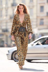 Model and Blogger Alexandra Lapp in an Animal Print Look wearing a leopard patterned jumpsuit in gold metallic by Maison Valentino, the Lou Camera Leather Crossbody Bag in black from Saint Laurent, Pigalle Follies 100 metallic crinkled leather Pumps in gold by Christian Louboutin and the Portugieser Chronograph watch by IWC.
