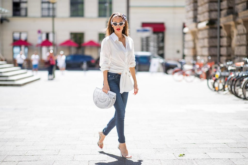 Alexandra Lapp in a Headband Style wearing La Chemise Olhao in off white by Jacquemus, blue AG Adriano Goldschmied denim, white Inez leather sandals by Saint Laurent, white Gaia's Ark bag by Cult Gaia, white Saint Laurent New Wave 213 Lily Sunglasses and a vintage Dior headband during the Berlin Fashion Week July 2018 on July 6, 2018 in Berlin, Germany.