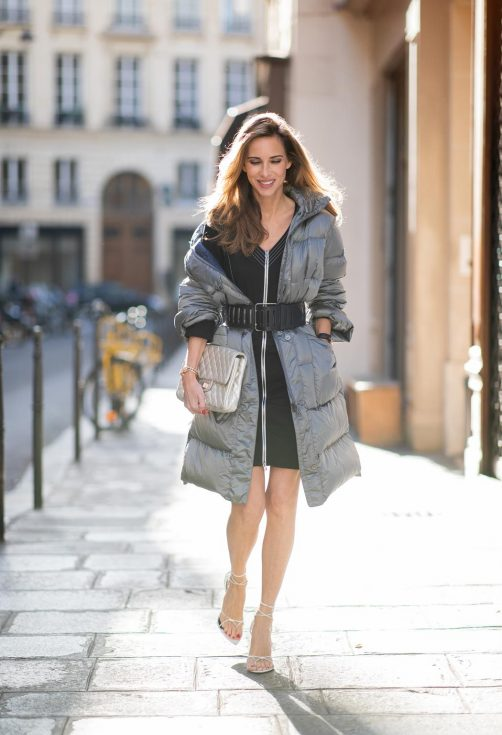 Alexandra Lapp in an Oversized Down Coat Look wearing a black shift dress with darts from Airfield, a long silver coat by Airfield, a black ripped Alaïa belt, white Inez leather sandals by Saint Laurent, a vintage silver Chanel clutch bag and the New Wave 213 Lily sunglasses in white from Saint Laurent during Paris Fashion Week Womenswear Spring/Summer 2019 on September 27, 2018 in Paris, France.