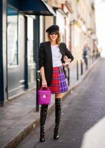 Alexandra Lapp in a Kilt Skirt Look wearing a long black boyfriend oversized blazer by Saint Laurent, a handmade Wodka Ogurez T-Shirt with a hand-painted print, a pleated patchwork tartan mini wool skirt from Versace, Frenchissima Alta Overknees in patent soft black leather by Christian Louboutin, Soft Berlin Crossbody Bag in Viva Lilac from MCM, vintage Chanel bakerboy cap in black and Neenah sunglasses from State Optical in black white is seen during Paris Fashion Week Womenswear Spring/Summer 2019 on September 29, 2018 in Paris, France.