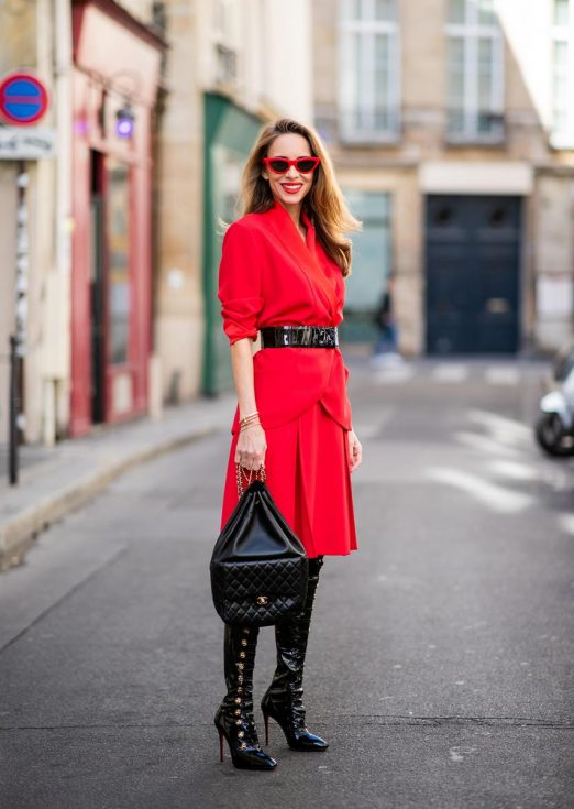 Alexandra Lapp in a Vinyl Overknee Boots Look wearing a long waisted blazer in red by Steffen Schraut, red high waist skirt with attached ribbon by Steffen Schraut, black patent leather waist belt by Gucci, Frenchissima Alta Overknees in patent soft black leather by Christian Louboutin, vintage Chanel backpack in black and red cat-eyed sunglasses by Céline during Paris Fashion Week Womenswear Spring/Summer 2019 on September 24, 2018 in Paris, France.