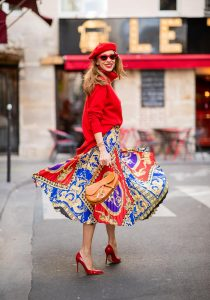 Alexandra Lapp seen in a Versace Skirt Look wearing a pleated printed midi skirt from Versace, a long red cashmere turtle neck pullover from Falconeri, a vintage Dior saddle bag in cognac, red pumps from Gianvito Rossi, a beret cap in red from Zara, red cat-eye shaped sunglasses from Celine during Paris Fashion Week Womenswear Spring/Summer 2019 on September 29, 2018 in Paris, France.
