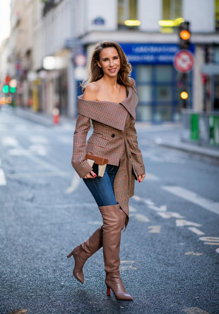 Alexandra Lapp wearing an Off-Shoulder Blazer Look with a plaid asymmetric off shoulder blazer from Monse, dark blue jeans from Rag & Bone, over knee boots in soft pink from Santoni, a Yuzefi Lola leather belt bag in brownish and black tones and brown sunglasses from State Optical during Paris Fashion Week Womenswear Spring/Summer 2019 on September 26, 2018 in Paris, France.