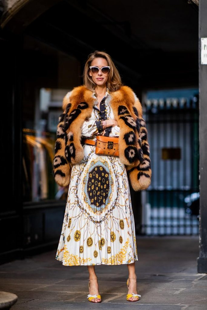 Alexandra Lapp in a Pattern Mix wearing a pleating chain patchwork print skirt and a matching shirt from Zara, a short fur jacket from Yves Salomon with an animal print, Metrisandal open-toe sandals from Christian Louboutin with tape-style straps, the Soft Berlin Belt Bag in Visetos by MCM in cognac and the Gucci cat-eye radiant ivory sunglasses during Paris Fashion Week Womenswear Spring/Summer 2019 on September 24, 2018 in Paris, France.