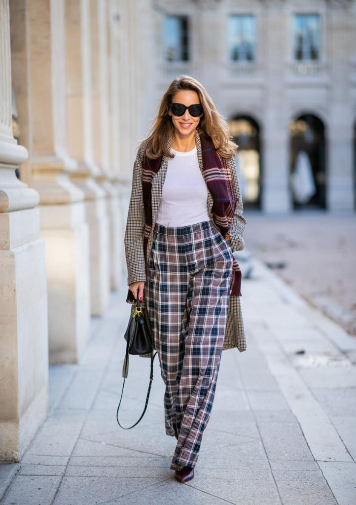 Alexandra Lapp in a Layered Look wearing a plaid oversized coat from SET fashion, a white T-Shirt from Vince, a Glenchek style scarf in dark red tones, wide plaid pants with a long leg in blue and brown tones from Tory Burch, boots in bordeaux from Gianvito Rossi and black Audrey sunglasses from Celine during Paris Fashion Week Womenswear Spring/Summer 2019 on September 27, 2018 in Paris, France.