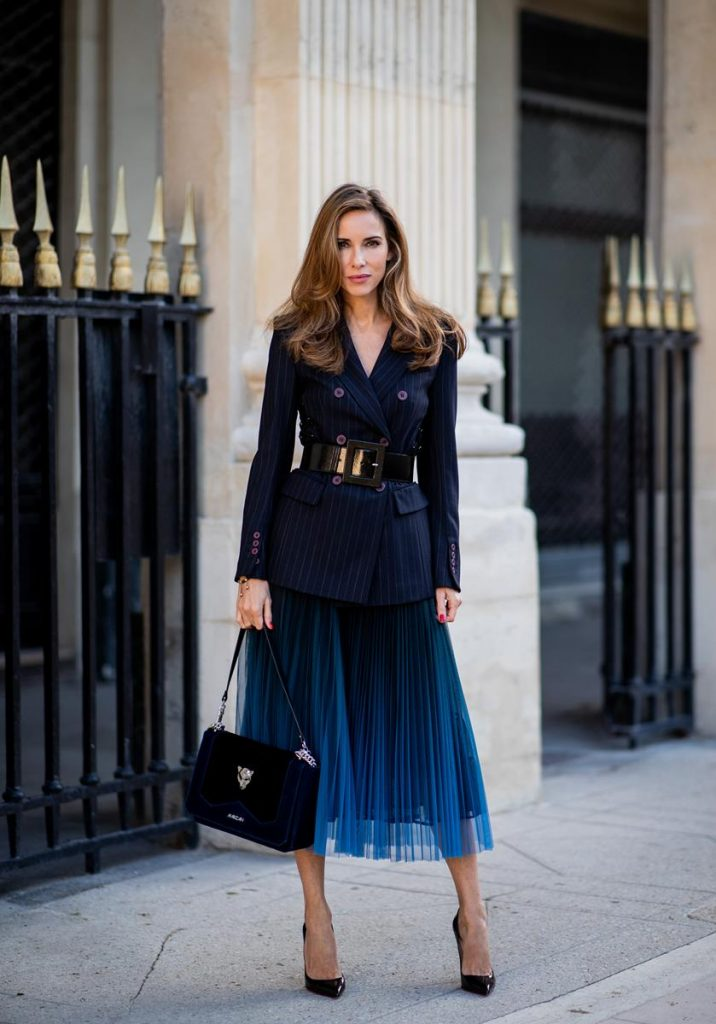 Alexandra Lapp in an All Blue Everything Look wearing a blue pleated skirt, navy striped blazer with belt and blue velvet bag all by Marc Cain, black heels from Christian Louboutin, a black lacquer waist belt by Dolce & Gabbana and black Audrey sunglasses by Céline seen during Paris Fashion Week Womenswear Spring/Summer 2019 on September 25, 2018 in Paris, France.