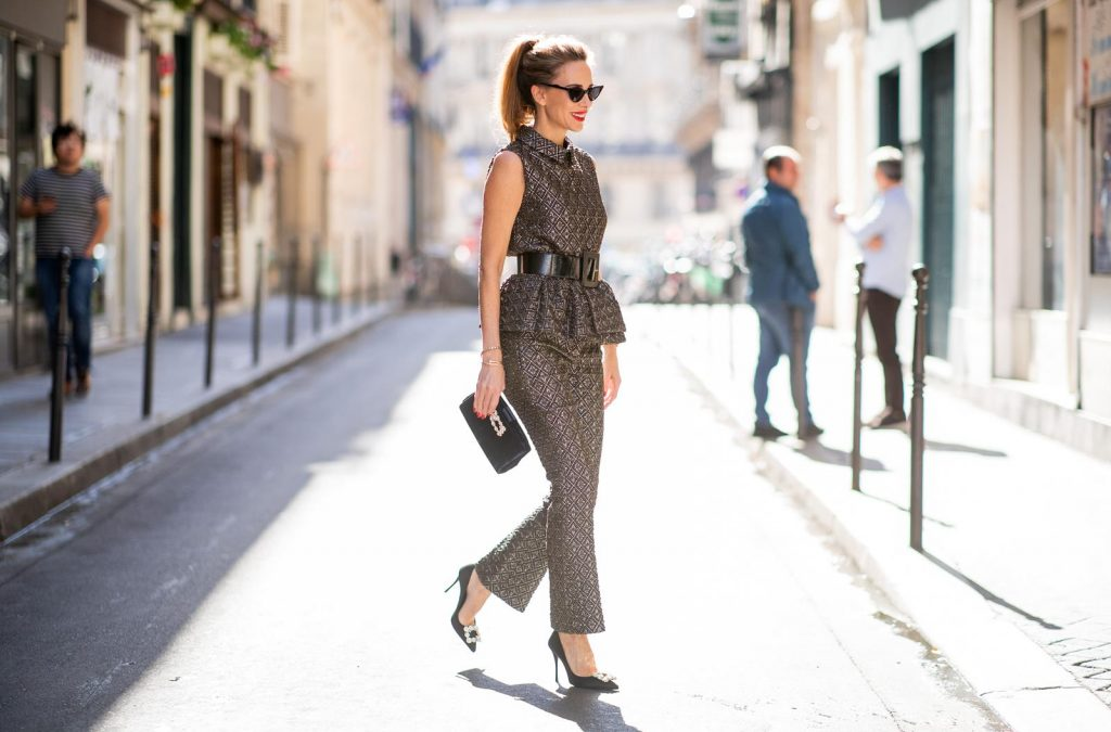 Alexandra Lapp in a Shiny Suit wearing a ruffled top with a collar and no arms from No21 in a shiny bronze and silver pattern with matching slim cut pants, black Flower Strass Buckle pumps by Roger Vivier, a lacquer waist belt from Dolce & Gabbana, black Soft Flowers Clutch by Roger Vivier and the Isabella black cat-eye shaped sunglasses from Illesteva.