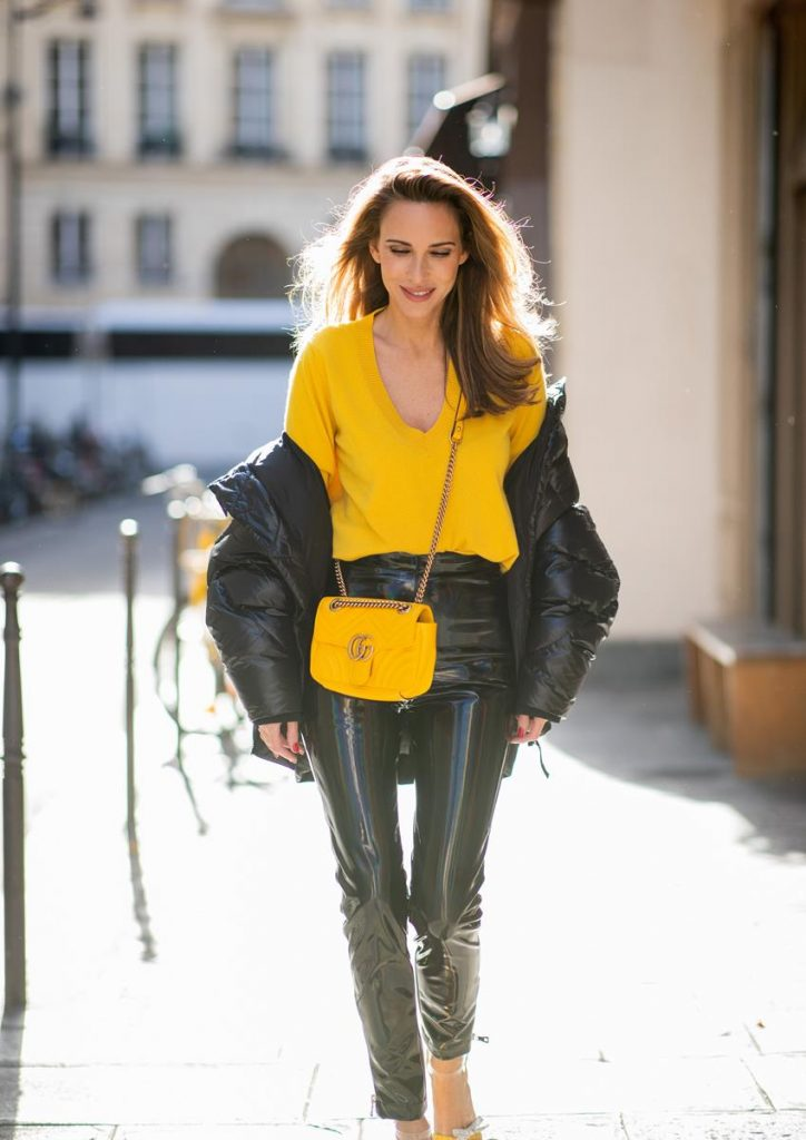 Alexandra Lapp in a Vinyl Pants Look wearing black zipped patent leather trousers from Balmain, a yellow v-neck knit jumper by Allude, shiny black down jacket by Ahirain, yellow Gucci Matelasse GG bag, yellow white Metrisandal open toe sandals with tape-style straps by Christian Louboutin and cat-eye shaped Isabella Sunglasses by illesteva during Paris Fashion Week Womenswear Spring/Summer 2019 on September 27, 2018 in Paris, France.