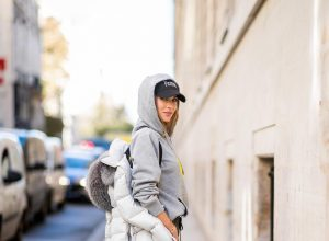 Alexandra Lapp in a Light Down Jacket Look wearing a light grey, fitted down jacket with inner carriers by Airfield, a handmade grey Hoodie with hand-painted print by Wodka Ogurez, black leather pants by SET, black Femme baseball cap from Balenciaga and black patent leather pumps by Christian Louboutin during Paris Fashion Week Womenswear Spring/Summer 2019 on September 24, 2018 in Paris, France.