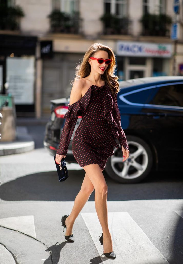 Alexandra Lapp in a One Shoulder Mini Dress Look wearing an one-shoulder ruffled fil coupe chiffon mini dress by Self-Portrait, black leather heels black sequined in the back from Roger Vivier, black Soft Flowers Clutch in silk by Roger Vivier and red cat-eye shaped sunglasses from Celine during Paris Fashion Week Womenswear Spring/Summer 2019 on September 25, 2018 in Paris, France.