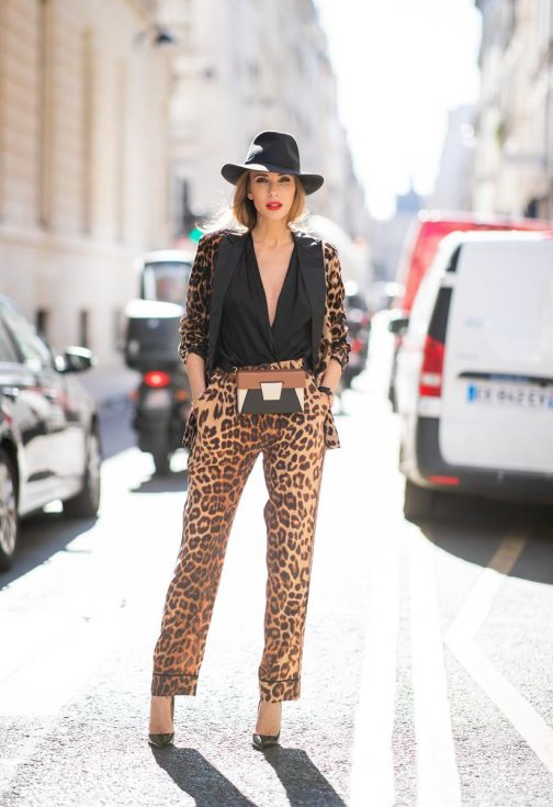Alexandra Lapp in a Leo Print Look wearing a velvet blazer with a satin collar in leopard print with matching satin leopard print trousers from Jadicted, a black satin top from Balmain with a wide cut out, the Lola color-block belt bag from Yuzefi, black pumps from Christian Louboutin and a black Alessandria medium-brim felt hat from Borsalino during Paris Fashion Week Womenswear Spring/Summer 2019 on September 25, 2018 in Paris, France.