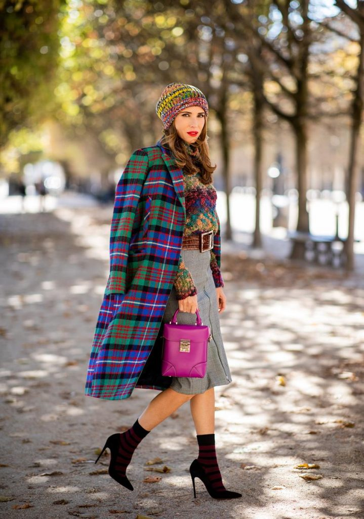 Alexandra Lapp in a Mixed Prints Look wearing a long multicolored plaid coat and a wool turtleneck multicolored sweater from Ouì, a black and white plaid slim cut skirt with a zipper up front from Ouì, a brown waist belt from Max Mara, black suede high heels from Christian Louboutin, the Soft Berlin Crossbody Bag in Viva Lilac from MCM, a multicolored wool hat from Missoni, purple black striped socks by H&M and the black Audrey sunglasses from Celine during Paris Fashion Week Womenswear Spring/Summer 2019 on September 25, 2018 in Paris, France.