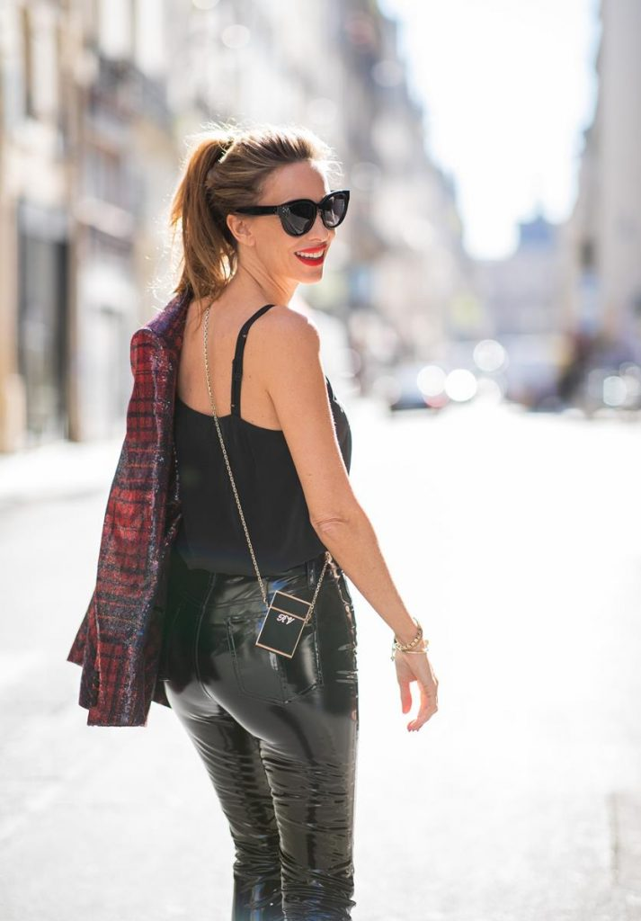Alexandra Lapp in a Faux Leather Pants Look wearing a long shiny sequin trimmed plaid blazer from Tommy Hilfiger, slim cut black vinyl pants from Rag & Bone, a black satin top from Jadicted, black lacquer pumps from Christian Louboutin, a Roger Vivier Stars Rivets leather cigarette case with a long golden chain and the black Audrey sunglasses from Celine during Paris Fashion Week Womenswear Spring/Summer 2019 on September 25, 2018 in Paris, France.