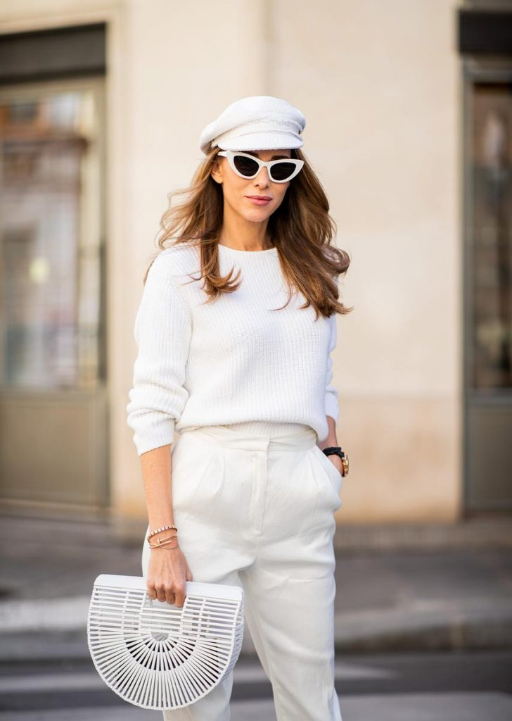 Alexandra Lapp in a White Vibes Look wearing white cropped trousers by Mansur Gavriel, a short knitted white pullover with a ring detail on the back from Ouì, white high heel boots from Zara, a white Baker Boy vintage hat from Chanel, a white Gaia's Ark bag by Cult Gaia and white Saint Laurent New Wave 213 Lily sunglasses during Paris Fashion Week Womenswear Spring/Summer 2019 on September 25, 2018 in Paris, France.