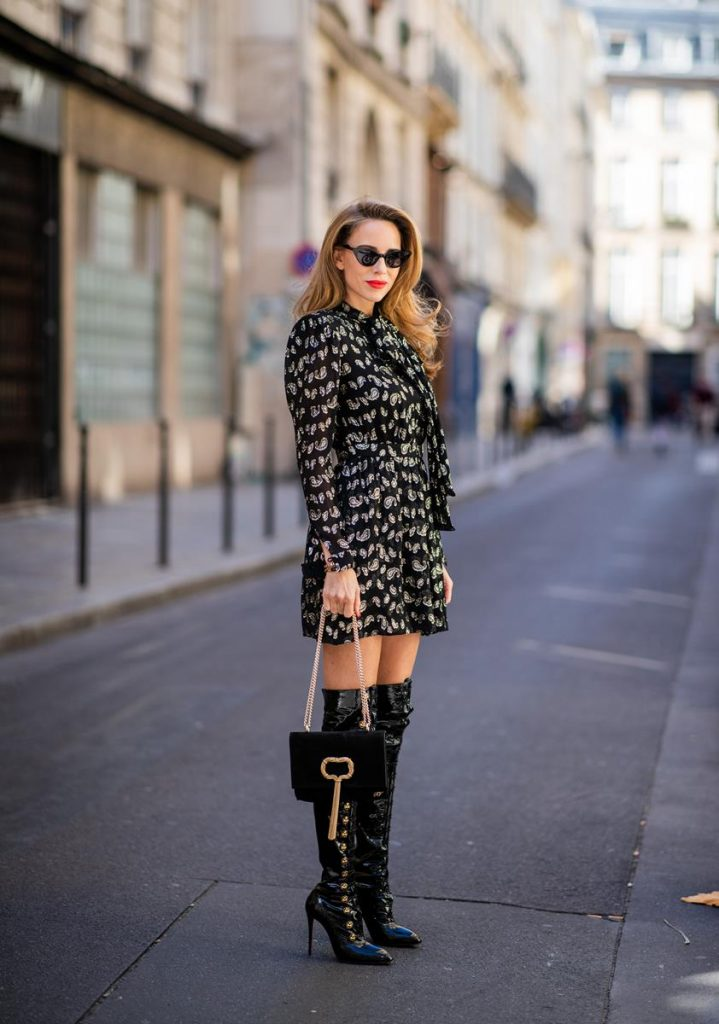 Alexandra Lapp in a Saint Laurent dress Look wearing a glitter paisley patterned dress by Saint Laurent, a reversible Shearling Trench Coat in a leopard look by Yves Salomon, Frenchissima Alta Overknees in patent soft black leather by Christian Louboutin, a Roger Vivier Stars Rivets leather cigarette case with a long golden chain and black Audrey sunglasses by Celine is seen during Paris Fashion Week Womenswear Spring/Summer 2019 on October 1, 2018 in Paris, France.