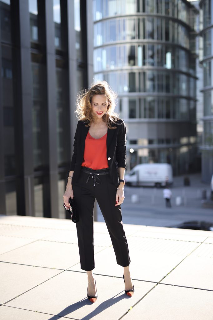 Alexandra Lapp in a Pop of Red Look wearing a stunning black blazer and pants combo from Airfield, mixed with a bright red silk top by Jadicted, an embroidered bag by Roger Vivier and a pair of Manolo Blahnik spiked heels.