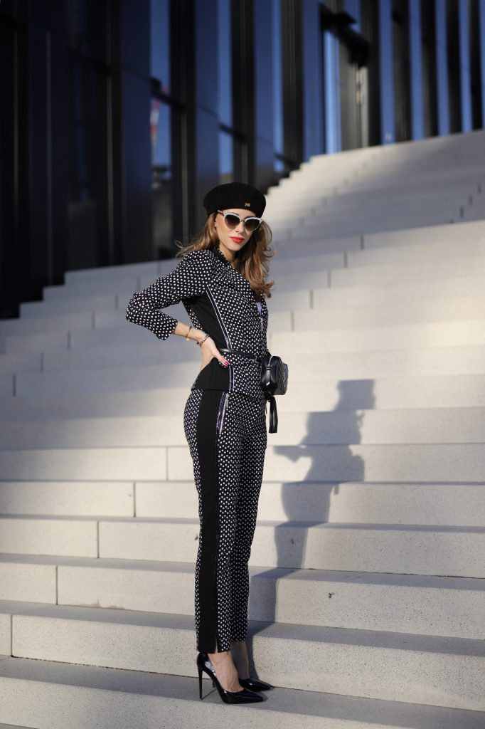 Alexandra Lapp in a Businesswoman Look wearing blazer and pants with polka dots in black white both from Airfield, red Jadicted silk top, black Lou leather belt bag by Saint Laurent, black patent leather pumps by Christian Louboutin, a black bakerboy cap by Dior and cat-eyed shaped vintage Gucci sunglasses with a white rim.