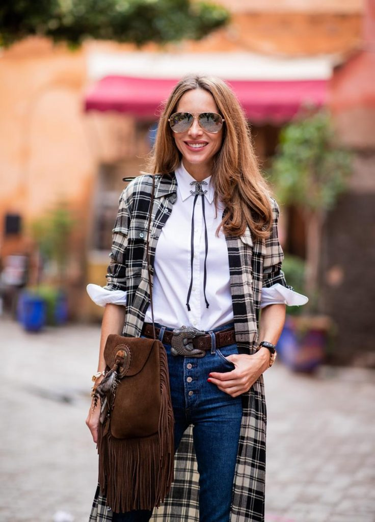 Alexandra Lapp in a Cowboy Style Look wearing a long checkered shirt dress from Polo Ralph Lauren, a white shirt from Loro Piana, light blue denims from Adriano Goldschmied, a brown suede leather bag with long fringes and a buckle with feathers from Saint Laurent, a black leather belt with white stitches from Isabel Marant, black Cowboy boots from Christian Dior, a silver Chanel brooch and mirrored sunglasses from Givenchy on November 25, 2018 in Marrakech, Morocco.