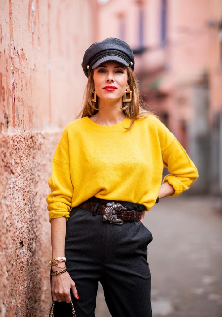 Alexandra Lapp in a Yellow Knit look, wearing a yellow crew-neck cashmere sweater from Jardin des Orangers, high-waisted trousers in dark grey by H&M, Graphic Flap Bag from Chanel in black/red/yellow/blue, brown lacquer Kieselstein Cord Crocodile belt, red lacquer pumps from Gianvito Rossi and dark grey nautical cap with buttons by ZARA on November 25, 2018 in Marrakech, Morocco.